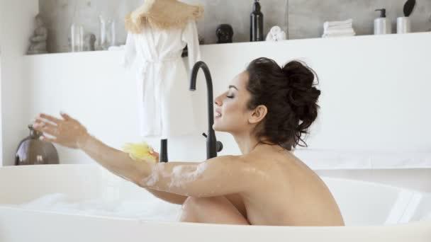 Žena se koupe s pěnou a myje si tělo.