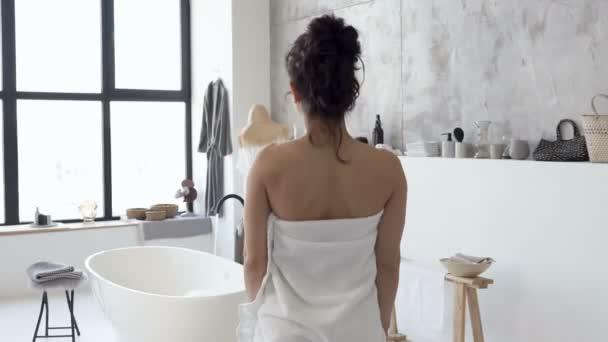 Žena oblečená v bílém ručníku, kráčející k vaně. Pohled zezadu. Ruční snímek.