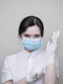 Fiatal nő beteg orvosi maszkban felvesz védő sebészeti steril kesztyűt a karján, szürke alapon, védelem a coronovírus ellen