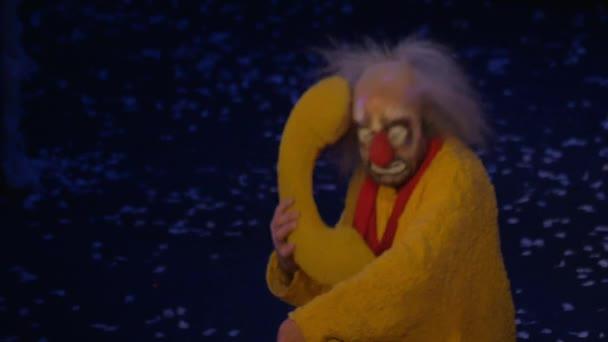 Na sněhu Ukázat Slava Polunin působí klaun v žlutém obleku a mluví na telefon, hračky