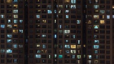 Lights in the windows of multistorey block of flats at night. Kuala Lumpur, Malaysia stock vector