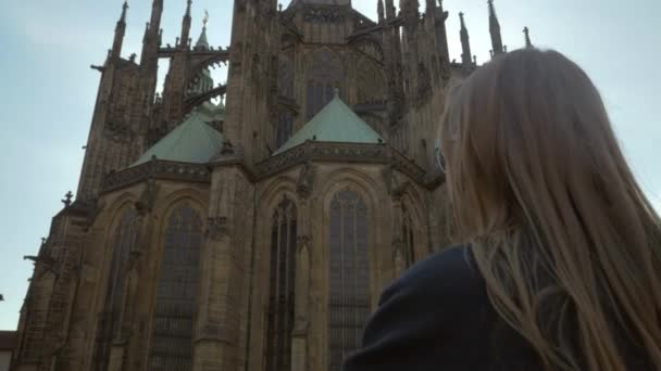 Woman tourist taking mobile photo of St. Vitus Cathedral, Prague