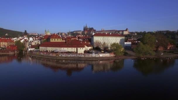 Aerial shot of waterside red rooftop buildings in Prague