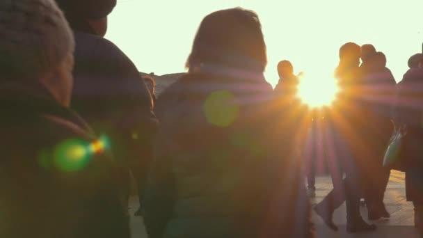 Anonymní dav procházky při západu slunce, pomalý pohyb