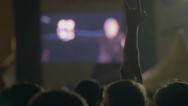 Muž diváka ukazující skála, rohy ďábel gesto před velkou obrazovku na venkovní hudební koncert