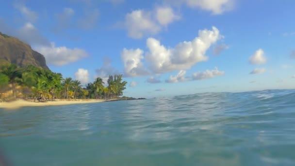 Koupání v jasné modré moře s výhledem na tropickou pláž