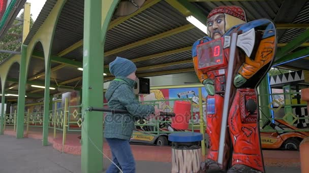 Slow motion view of small boy hitting with toy hammer game in amusement park, Vienna, Austria