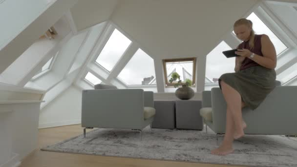View of young blond woman sitting on the side of arm chairs using tablet inside of room in a Cube house. Rotterdam, Netherlands