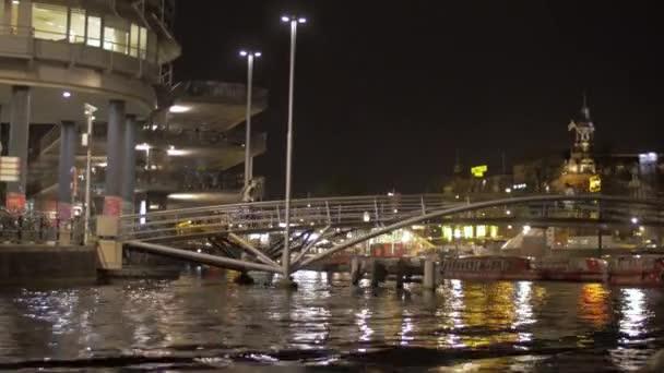 Pohled na přesun na lodi podél řeky Amstel za malý most pro pěší, Amsterdam, Nizozemsko