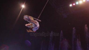 Letecká umělec dělat akrobatické aktu proti barevné fontány, akrobacie, Moskva, Rusko