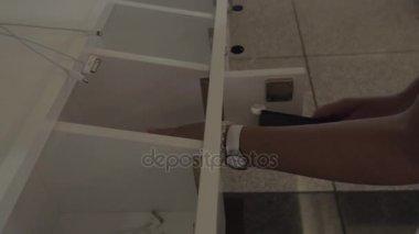 Žena opouští mobil do skříňky pro nabíjení