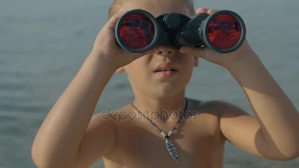 Lassított nézet a távcsővel szemben homályos tengerre néz kisfiú