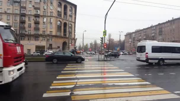 Moskevské ulice s provozem vozu na mokré silnici a hasice kolemjdoucí, Rusko