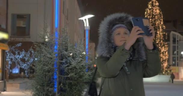 Žena buňka focení na ulici s vánoční osvětlení