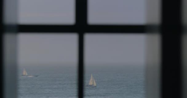 Plachetnice a frézy v moři, pohled z okna