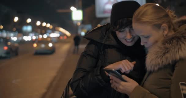 Women watching something on mobile while waiting at bus stop in the evening