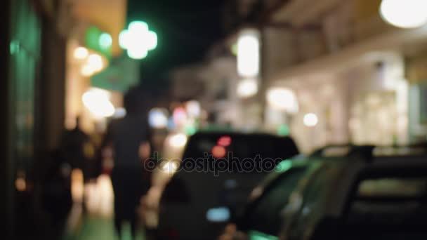 Nachtstadtstraße mit geparkten Autos und beleuchteten Transparenten