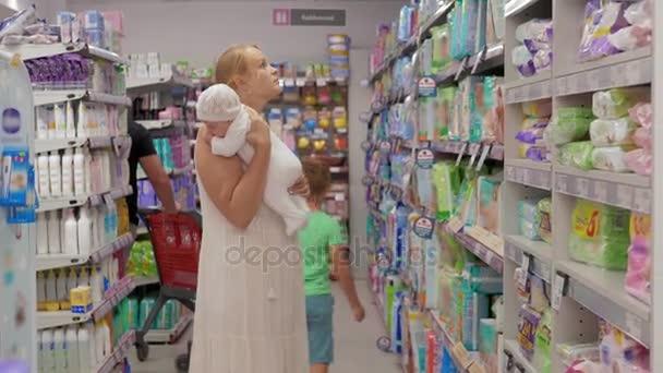 Matka s dětmi nakupovat a nákup plen pro miminko v supermarketu