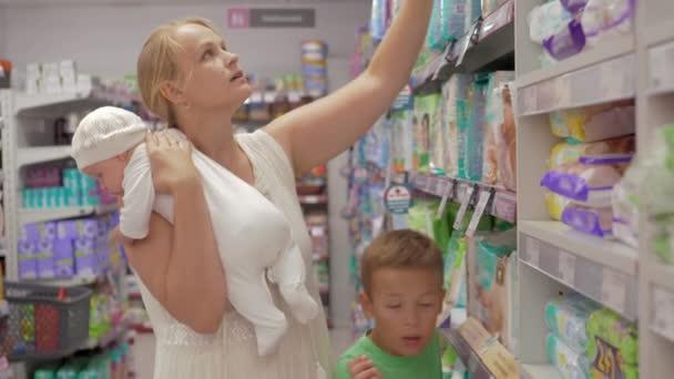Žena s syn a dcerka nákup plenek v úložišti