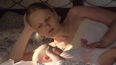 Femme tenant un b b qui a couch sur un lit vid o wavebreakmedia 21498781 - Coucher bebe sur le cote ...