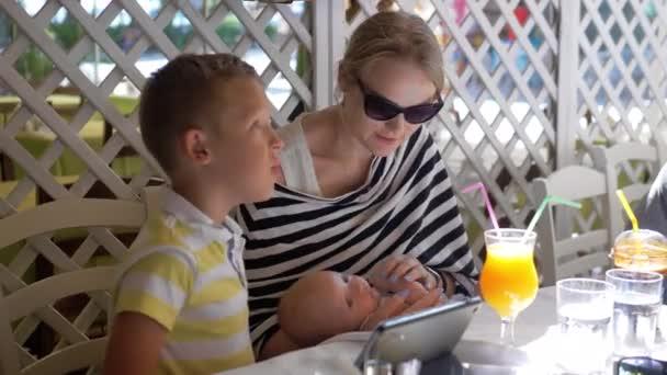 Nő baby és idősebb gyermek kávézóban nyári napon