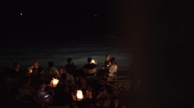 People enjoying evening in beach cafe at the shore