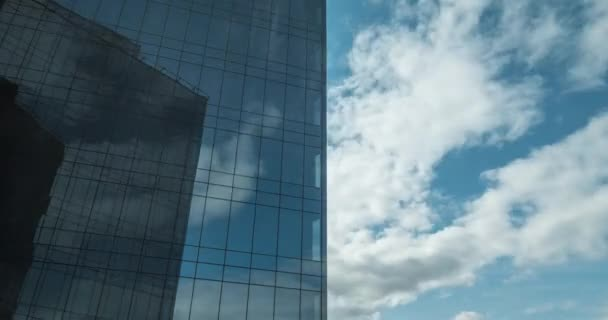 Timelapse of clouds moving and reflecting in glassy skyscraper
