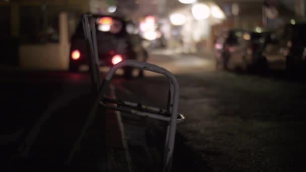 Ulice ve městě v noci. Výstřední židle v popředí