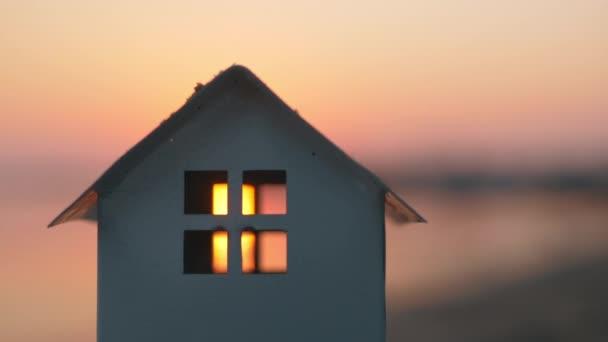 Model domu na pláži při západu slunce