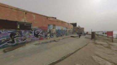 Man with dog walking along graffiti wall on sea front