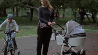 Mother walking with baby and elder son outdoor