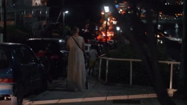 Woman having evening walk with baby and elder son