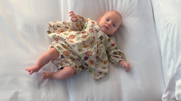 Az ágyon három hónapos kislány