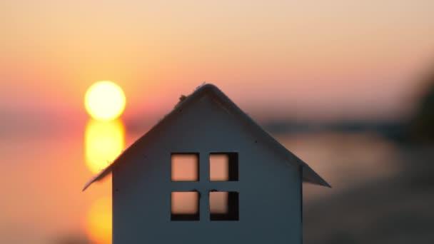 Hausmodell gegen den Sonnenuntergang