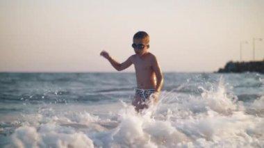 Boy and splashing sea waves