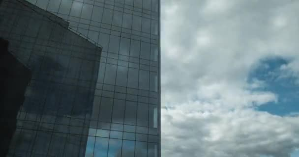 Timelapse of sailing clouds reflecting in glassy skyscraper