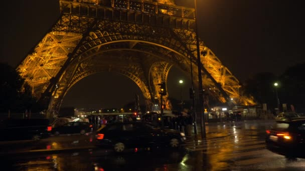 Paris street ar rainy night. Cars driving and people crossing the road