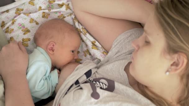 Mutter schläft beim Säugen von Neugeborenem
