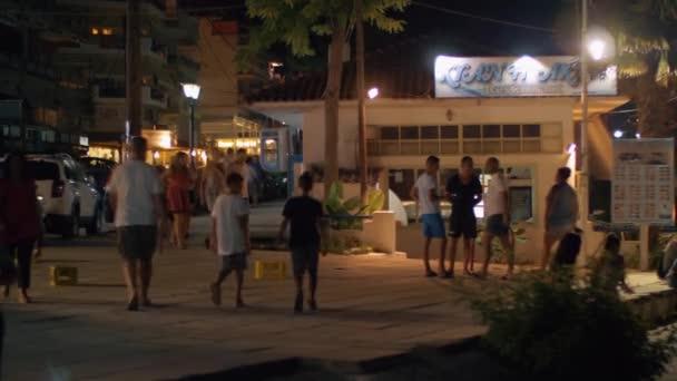 Lidí, kteří jdou na ulici noci Nea Kallikratia Řecko