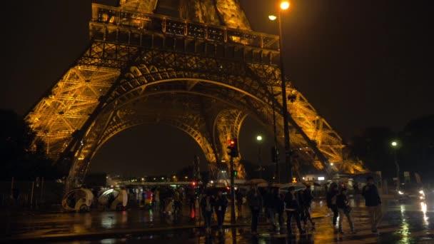 Lidé přes silnici blízko: Eiffel Tower v deštivé noci v Paříži