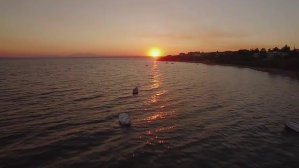 Letecká západ slunce scéna moře s lodí a letoviska na pobřeží, Řecko