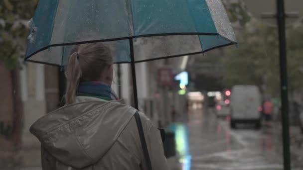 Frau mit Regenschirm am Herbstabend
