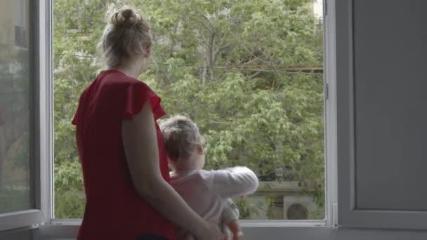 Máma s dcerou na vzduchu v otevřeném okně při izolaci koronaviru