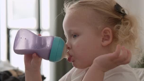 Toddler girl drinking milk from the bottle