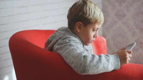 Little blonde boy playing and touching a table at home.