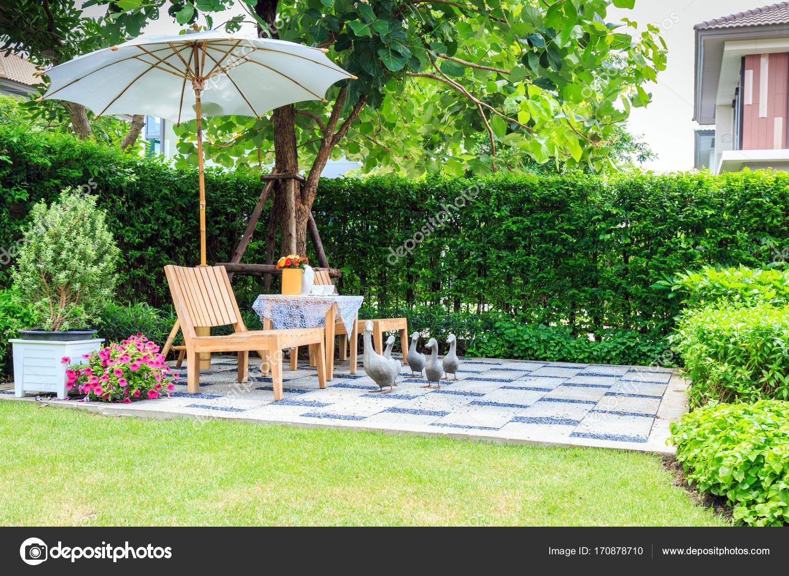 ensemble de thé sur un banc de pierre dans un jardin fleuri