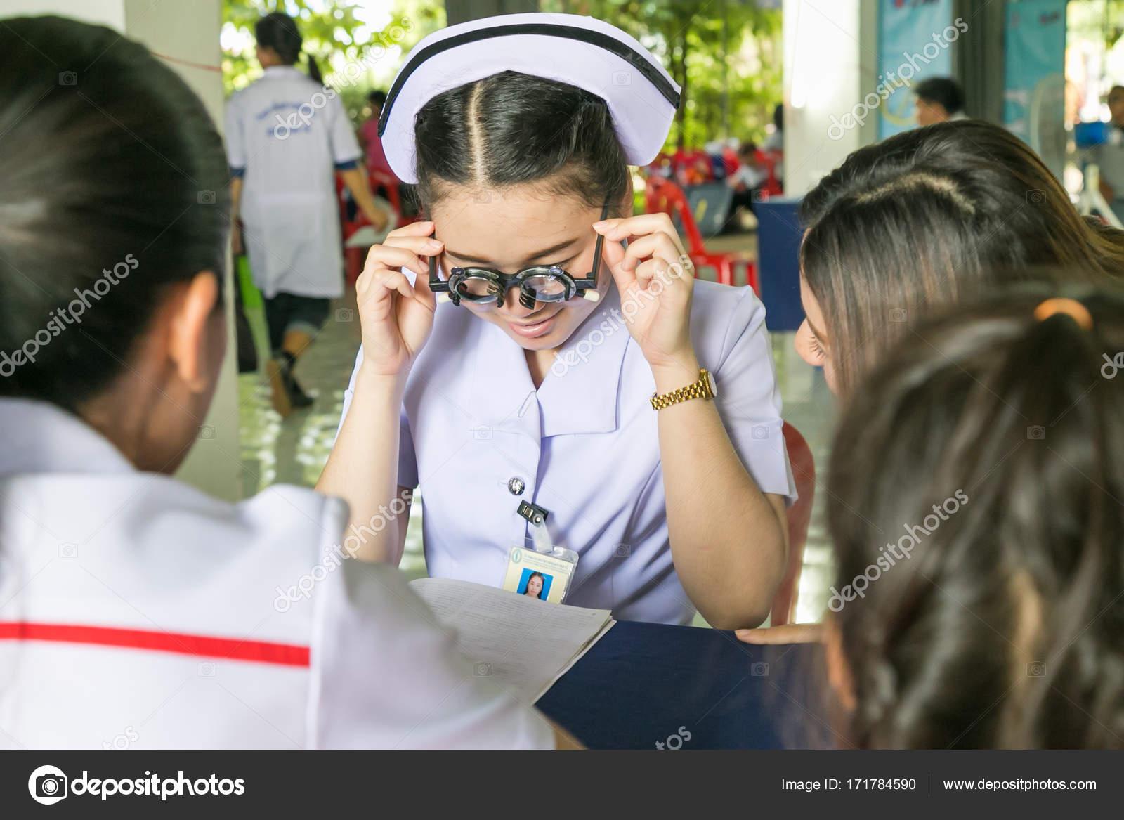Una enfermera joven asiático haciendo pruebas de visión utilizando ...