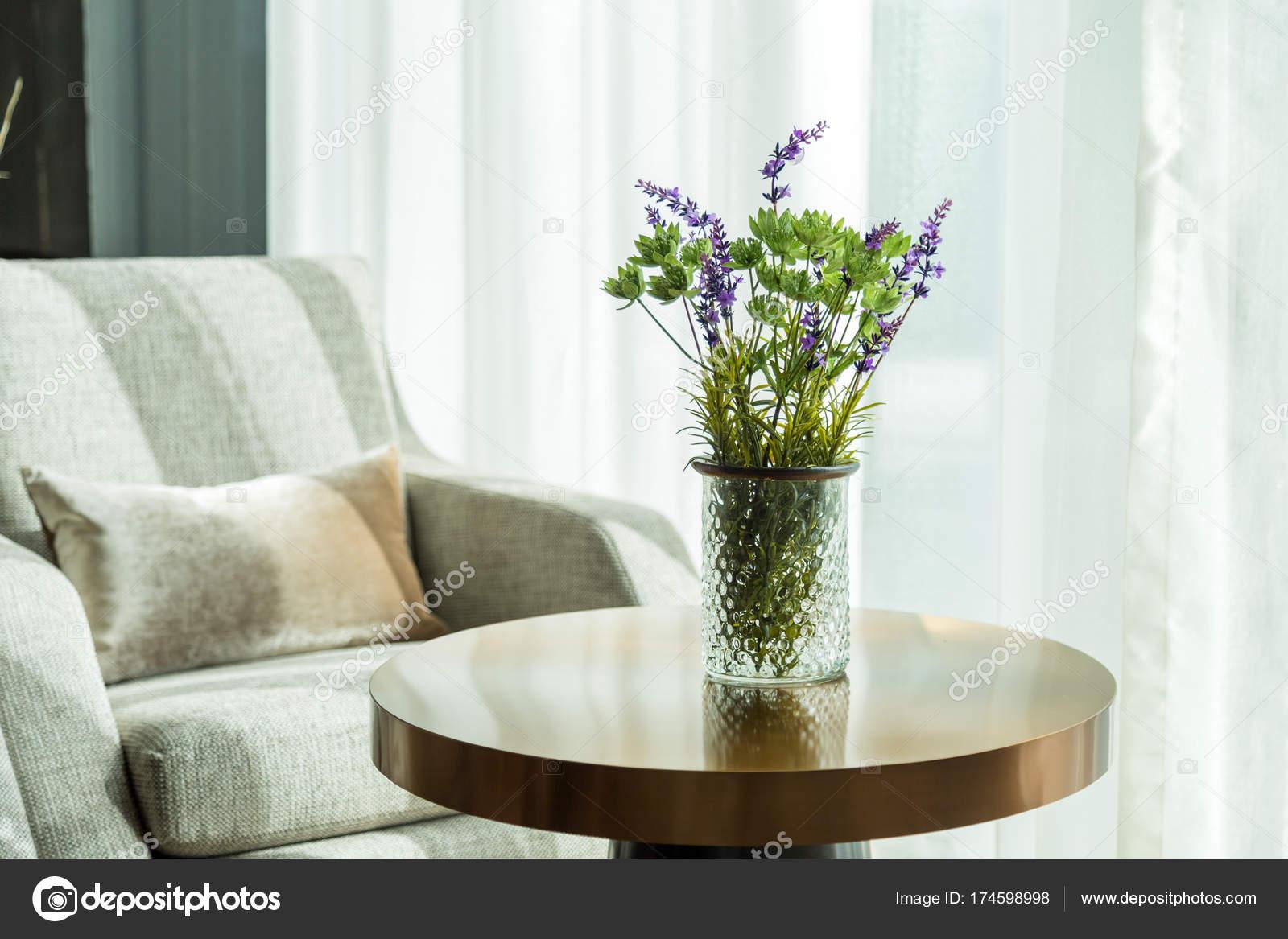 Grüne Blumen und lila Blumen in Vase auf dem Tisch im Wohnzimmer ...