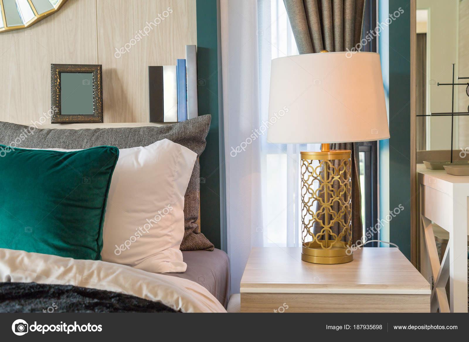 Une lampe à être côté un lit avec des rideaux dans la chambre ...