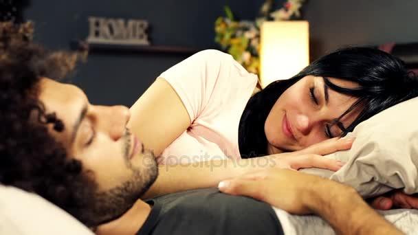 Žena začíná spát blízko přítel drží ruce v posteli
